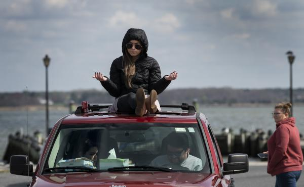 A member of Jesus' Church prays on top of a car during a Sunday church service held at Great Marsh Park in Cambridge, Maryland, on March 22, 2020.