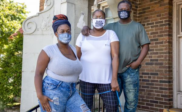 Heavenly Pettigrew, left, and her parents Stephanie and Robert outside their two-bedroom rental apartment in Milwaukee. Without assistance from the nonprofit Community Advocates, the family likely would have faced eviction after the pandemic forced Robert