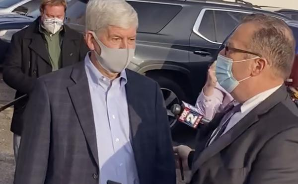 In this image taken from video, former Michigan Gov. Rick Snyder, left, with his lawyer, Brian Lennon, leave Genesee County Court in Flint, Mich., after a initial court appearance via Zoom on two misdemeanor counts of willful neglect of duty in connection