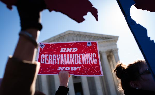 An activist holds a sign outside the U.S. Supreme Court in 2019.