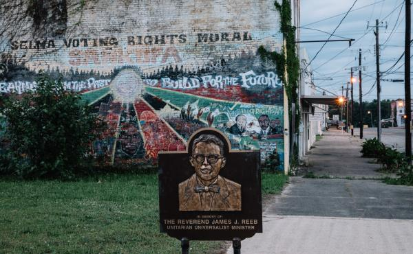 A memorial to the Rev. James Reeb, attacked near this site in 1965, stands in front of a faded civil rights mural in Selma, Ala.