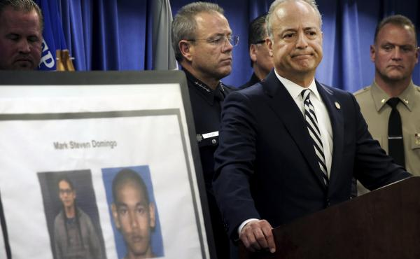 U.S. Attorney Nick Hanna stands next to photos of Mark Steven Domingo during a news conference in Los Angeles on Monday. Federal prosecutors said Domingo had planned to bomb a white supremacist rally as retribution for the New Zealand mosque attacks but w