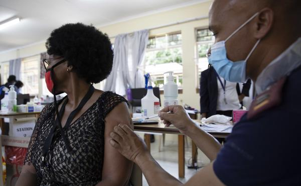 A health care worker looks away as she's immunized with Johnson & Johnson's COVID-19 vaccine at Klerksdorp Hospital in Klerksdorp, South Africa, on Feb. 18.