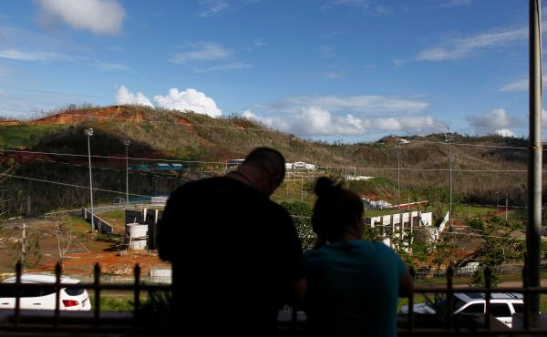 Two evacuees look out from the entrance of the Luis Muñoz Marín public school last week in Barranquitas, Puerto Rico. Many people from Barranquitas have been living in a shelter set up in the school since Hurricane Maria destroyed their homes in Septemb