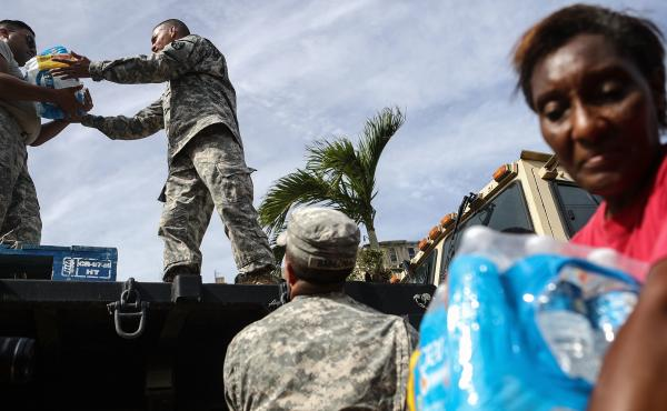 U.S. Army soldiers pass out water, provided by FEMA, to residents in a neighborhood without grid electricity or running water in San Isidro, Puerto Rico, on Oct. 17, 2017.