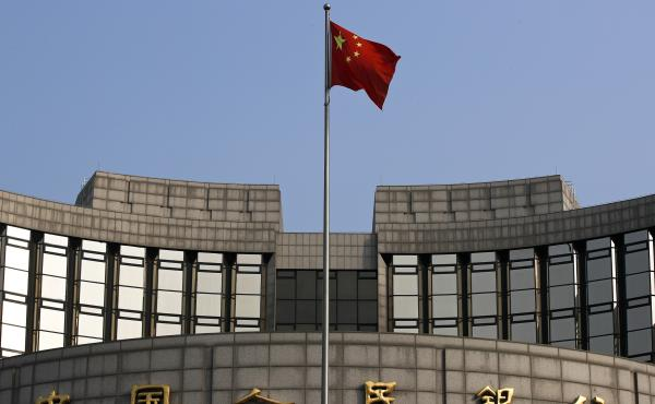 A Chinese national flag flutters in front of the People's Bank of China, the country's central bank, in Beijing. The bank plans to launch a cryptocurrency.