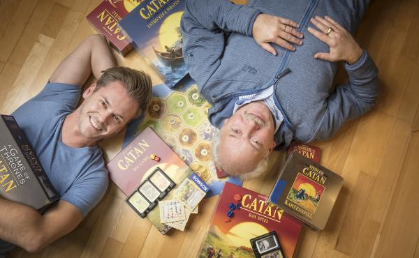Klaus Teuber, creator of the popular board game Catan, with his son Benjamin Teuber, a managing director at Catan Inc. Celebrating the 25th anniversary of the game's launch, the elder Teuber has released an autobiography, My Way to Catan.
