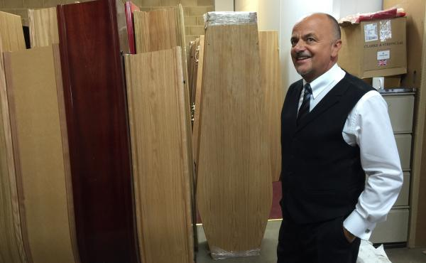 John Harris, who runs the T. Cribb & Sons funeral home in the East End of London, stands in the coffin warehouse. The key to staying in business in the changing district is to diversify and specialize, he says.