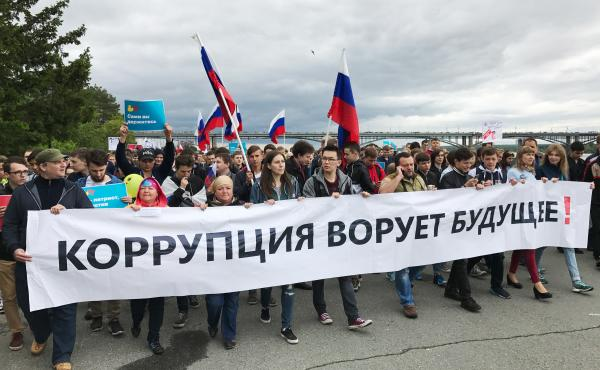 """Anti-government protesters march in Novosibirsk, the capital of Siberia and Russia's third most populous city, with a banner reading """"Corruption steals the future!"""""""