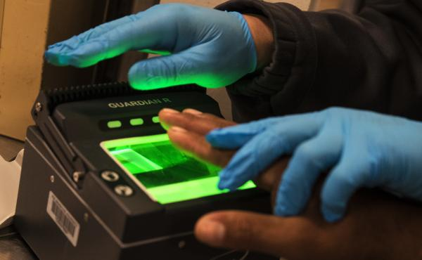 Immigration and Customs Enforcement agents take fingerprints while processing apprehended immigration fugitives inside the ICE staging facility in Los Angeles on April 18, 2017. Earlier this year ICE agents searching for an undocumented farmworker stopped