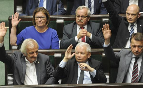 Law and Justice party leader Jaroslaw Kaczynski (bottom row center) and fellow party members vote Thursday to approve a law giving the president control over the Supreme Court.