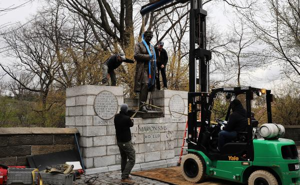 A statue of surgeon J. Marion Sims is taken down from its pedestal in Central Park on Tuesday. A New York City panel decided to move the controversial statue after outcry, because many of Sims' medical breakthroughs came from experimenting on enslaved bla