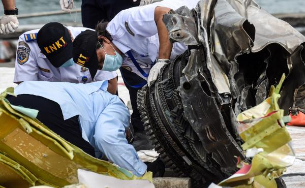 Indonesia's National Transportation Safety Committee (KNKT) officers check debris last month from the crash of a Sriwijaya Air Boeing 737-500 in  Jakarta, Indonesia.