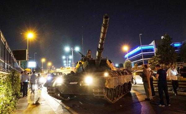 People gather near a Turkish army tank in Istanbul on July 16, after a group within Turkey's military attempted a coup. Since then, more than 100,000 people been detained, fired or suspended from their jobs on suspicion of sympathizing with or aiding the
