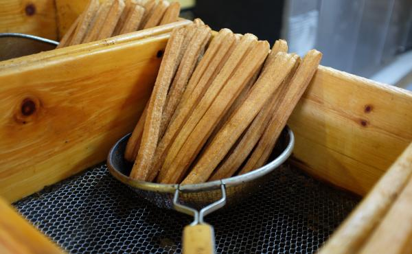 Fresh churros are drained before they are stacked on trays for vendors to pick up.
