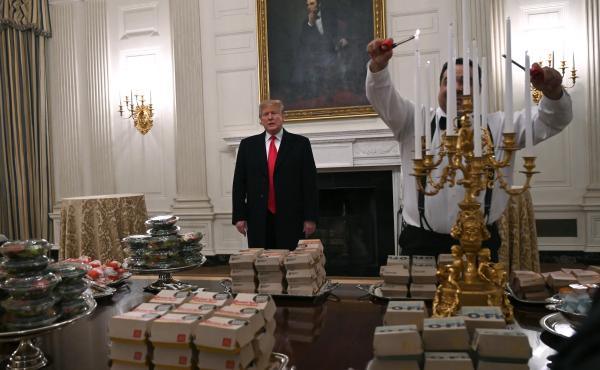 President Trump talks to the press about the table full of fast food laid out in the State Dining Room of the White House for a reception for the Clemson Tigers.