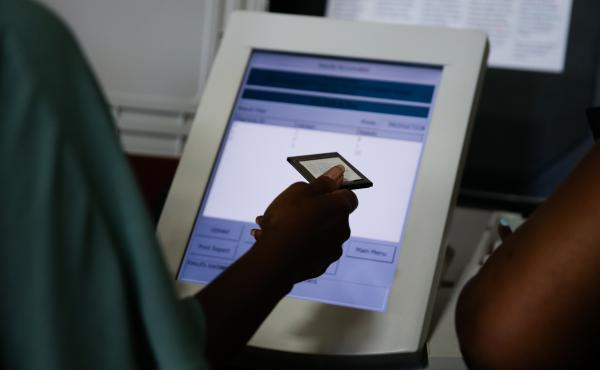 An election official holds an electronic voting machine memory card following the Georgia primary runoff elections at a polling location in Atlanta on July 24, 2018. A group of Georgia voters is suing the state, saying that the electronic machines are not