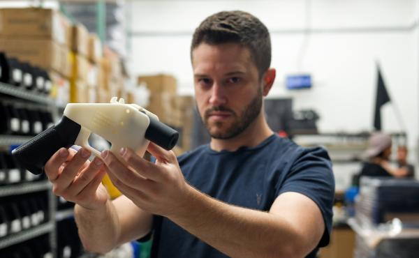 "Cody Wilson, owner of Defense Distributed, holds a 3-D printed gun, called the ""Liberator"" in his factory in Austin, Texas, on Aug. 1."