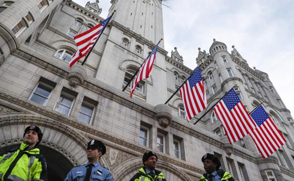 Police stand guard outside the Trump International Hotel, blocks from the White House last year. The hotel has become a center piece in lawsuits claiming the president is profiting from the office.