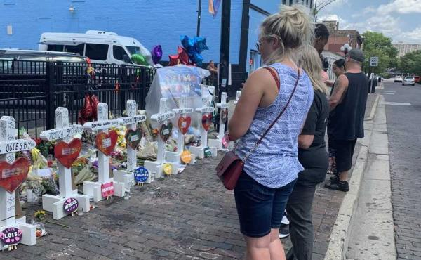 Onlookers in Dayton, Ohio, mourn the nine people who died when a gunman opened fire on a crowd outside a popular bar in the city's Oregon District this month.