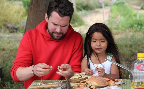 "Daniel Klein picks meat from crabs with the young daughter of a former strawberry picker in Oxnard, Calif., for an episode called ""A Day In The Life."""