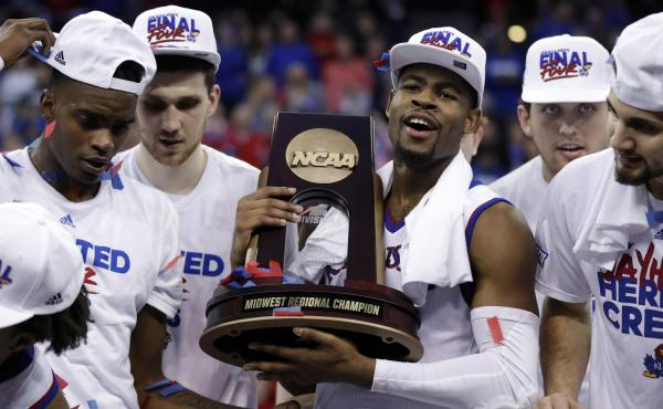 Kansas' Malik Newman holds the trophy after defeating Duke in a regional final game in the NCAA men's basketball tournament Sunday in Omaha, Neb. Kansas won 85-81 in overtime.