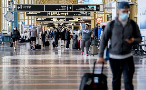 Mask-wearing travelers head through Reagan National Airport in Arlington, Va., in May. More than 70% of reports to the FAA of unruly passengers this year were related to people failing to comply with mask mandates and causing a disruption as a result.