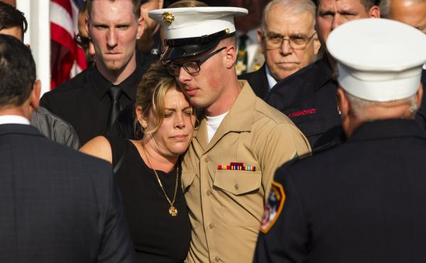 Erika Starke, left, is comforted by her son, Michael Haub, as they attend a second funeral service for New York Fire Department firefighter Michael Haub, in Franklin Square, N.Y. The New York City medical examiner identified more of his remains recovered