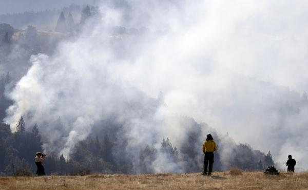 A firefighter (center) and two onlookers watch a smoldering wildfire from a hilltop in Oakville, Calif., on Sunday.