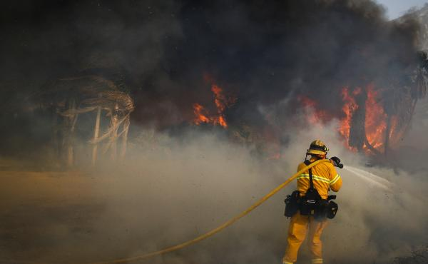 A firefighter battles a wildfire at Faria State Beach in Ventura, Calif., Thursday.