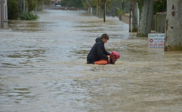 A firefighter helps a youngster reach safety in a flooded street during a rescue operation following heavy rains that saw rivers bursting their banks in Trèbes, near Carcassonne, in southern France.