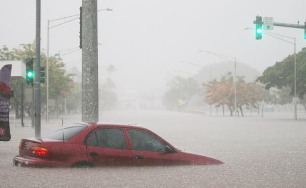 A car is stuck partially submerged in floodwaters from Hurricane Lane rainfall on the Big Island on Wednesday in Hilo, Hawaii.