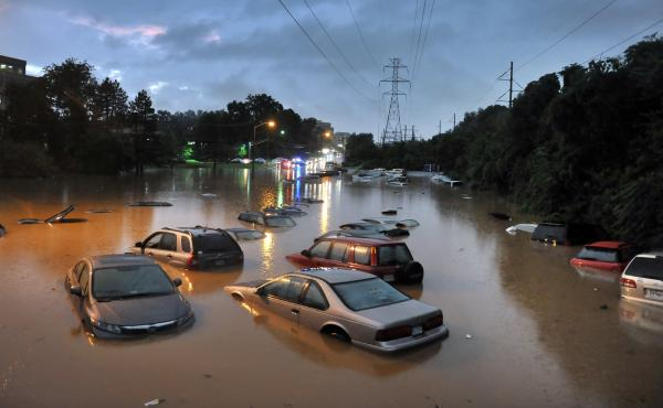 Scenes after heavy rainfall flooded a commuter parking lot in Reston, VA with some cars completely submerged.