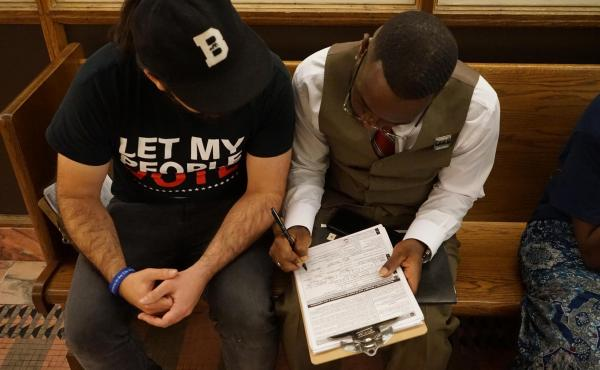 Dolce Bastien (right) registers to vote after getting his rights restored in Miami.