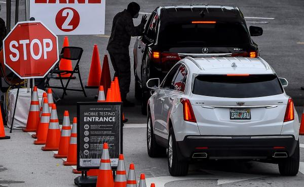 People wait for a COVID-19 test at a walk-in and drive-through coronavirus testing site in Miami Beach, Fla. on Wednesday. Florida set its single-day coronavirus death record of 173 on Thursday.