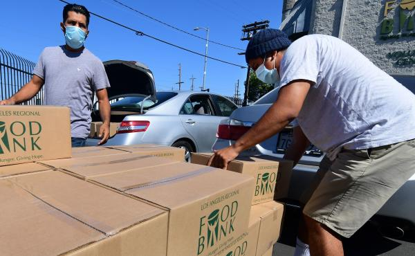 People load their vehicles with boxes of food at a Los Angeles Regional Food Bank earlier this month in Los Angeles. Food banks across the United States are seeing numbers and people they have never seen before amid unprecedented unemployment from the COV