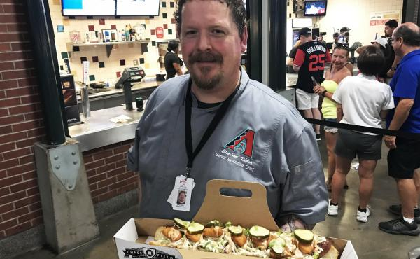 Stephen Tilder, the executive chef at Chase Field in Phoenix, holds the SI Cover Dog, a collaboration with a Sports Illustrated reporter.