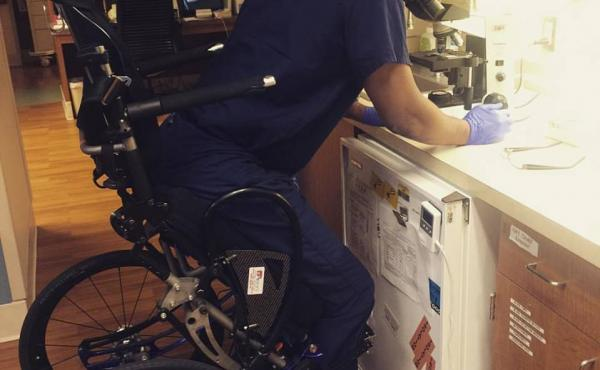 Feranmi Okanlami, now a doctor, became partially paralyzed after an accident in 2013. He says adjustments for his disability during his training, like this standing in frame chair, helped him succeed. A new report finds variability in medical institution