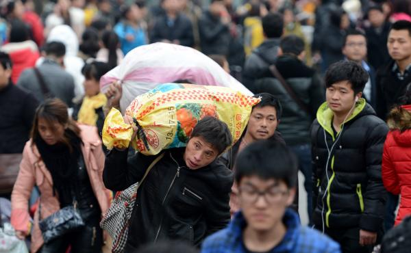Passengers go to the Nanchang railway station in eastern China in February 2014, at the end of the Chinese New Year holiday. In the past, it was often the only time of year that migrant workers were able to return home. Now, economic pressures on factorie