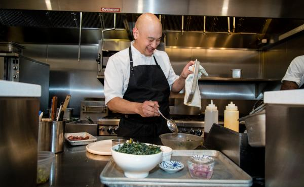 Tim Ma prepares a duck confit salad at his restaurant, Kyirisan, in Washington, D.C. Ma says being mindful about reducing food waste is an integral part of his philosophy in the kitchen — not just for environmental reasons but also for profitability.