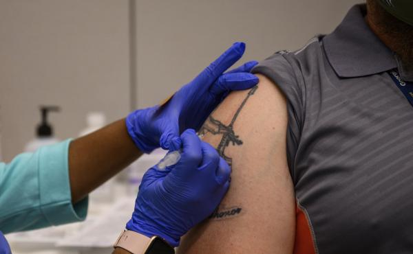 A Georgia Tech employee receives a Pfizer coronavirus vaccination on the campus April 8. For a number of Americans, getting their shots is as easy as showing up to their workplace as some companies and institutions provide on-site vaccinations to their em