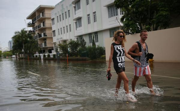People walk through a flooded street in in Miami Beach, Fla., in 2015. The city is eyeing $500 million in infrastructure upgrades, installing 80 new pumps over a decade to redirect floodwaters back to the ocean.