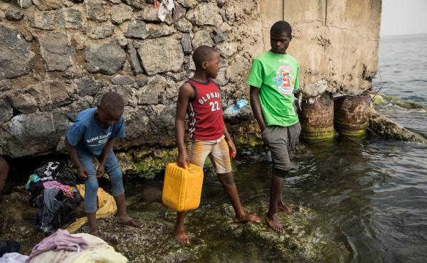 "Pascal Bitasimwa, 12, of Goma (in the red shirt) goes to Lake Kivu to fill up jerrycans with water. ""This takes me much of my time,"" he says. ""Instead of going to study, I come first to take water."""