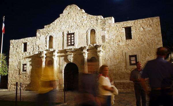 Visitors walk around the outside of the Alamo in San Antonio.