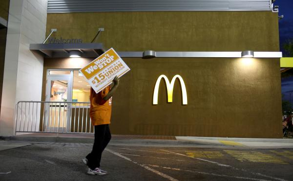 """Protesters gather at a McDonald's to ask for higher wages on April 15, 2015 in Miami Gardens, Fla. Food labor advocate Saru Jayaraman writes in a new book that the company has taken the """"low road"""" and lobbied extensively for lower wages and working condit"""