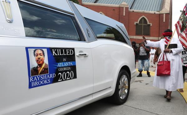 People gather near a hearse carrying Rayshard Brooks' body after his June 23 funeral at Ebenezer Baptist Church in Atlanta.