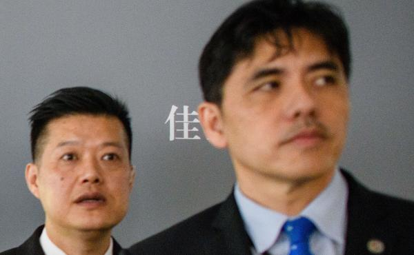 """This 2017 photo shows the man on the right, identified by local Hong Kong media as former CIA agent Jerry Chun Shing Lee, standing in front of a member of security at the unveiling of Leonardo da Vinci's """"Salvator Mundi"""" painting at the Christie's showroo"""