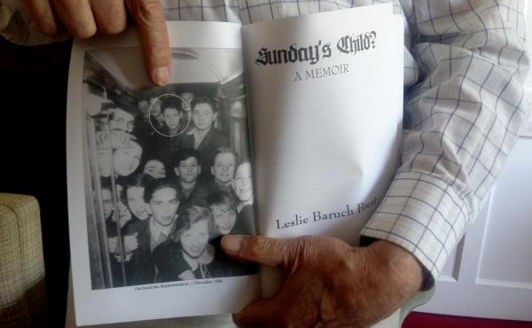 Leslie Brent, 90, a retired immunology professor who came to Britain as a Jewish child refugee via Kindertransport in 1938, holds his autobiography, showing a photo of himself and other Kindertransport children.