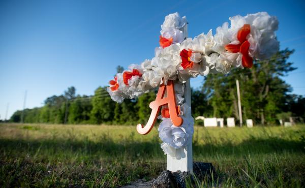 A cross with flowers and a letter A sits at the entrance to the Satilla Shores neighborhood where Ahmaud Arbery was shot and killed.