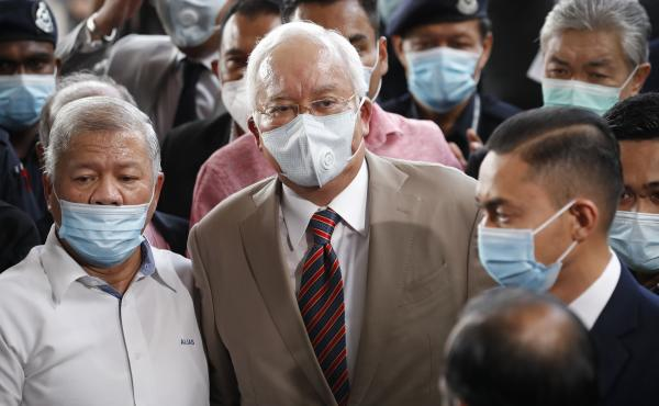 Former Malaysian Prime Minister Najib Razak (center), wearing a face mask with his supporters, arrives at the courthouse in Kuala Lumpur, Malaysia, on Tuesday. Najib was found guilty of corruption in the first of several trials linked to the multibillion-